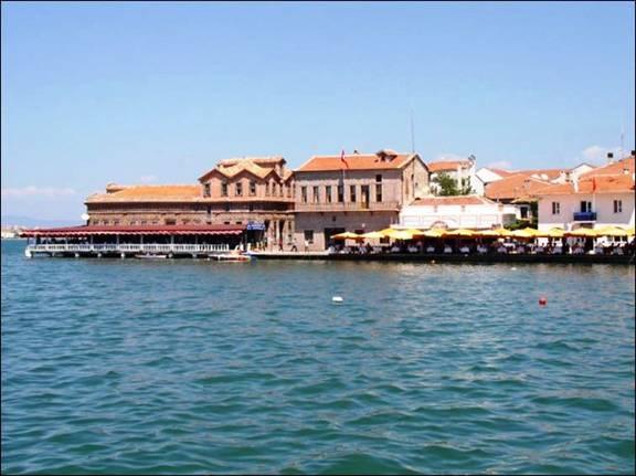 Εικόνα 2: Στη προκυμαία τα παλιά ελληνικά καφενεία, με το γωνιακό του «Κανέλλου» και το μεσαίο το Δημαρχείο του Αϊβαλιού.