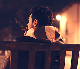 Man alone smoking in bench